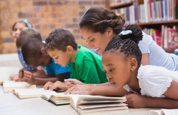 Maestra enseñando a estudiantes a leer en el Día Internacional de la Alfabetización.